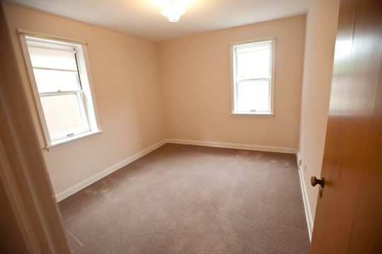 Looking into the carpeted bedroom with two windows