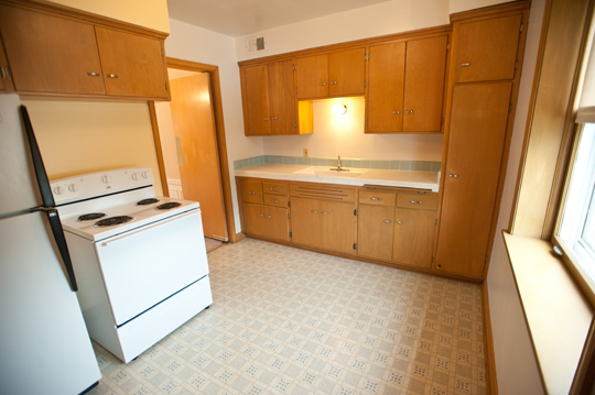 Kitchen room with wood cabinets and white fridge and stove
