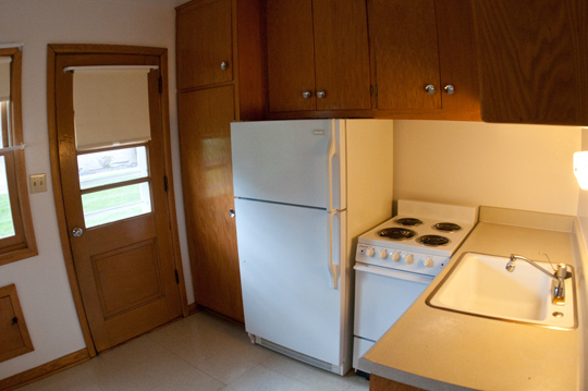 Kitchen with fridge, stove, and sink with back door