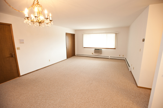 Carpeted living room with chandelier